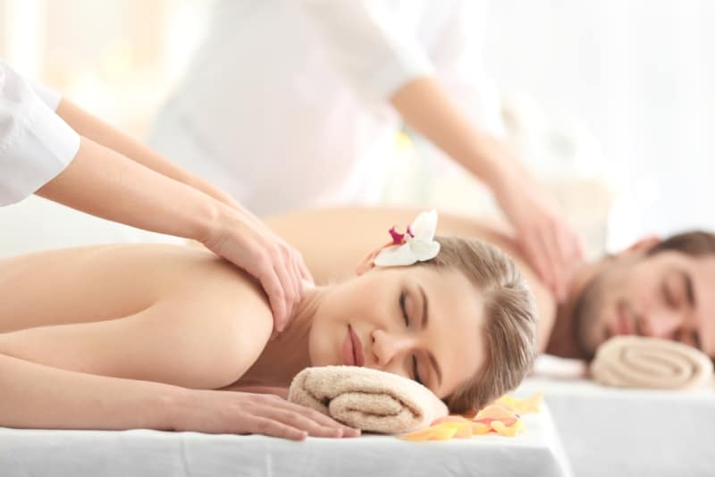 man and woman getting back massage at spa