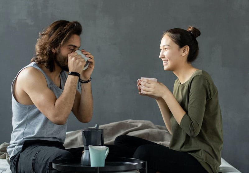 couple having coffee in bed while chitchatting