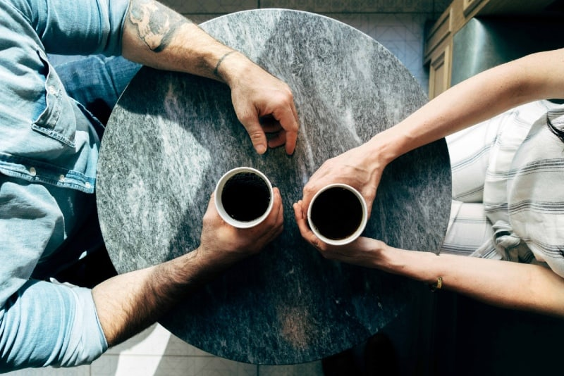 man and woman holding cups of coffee
