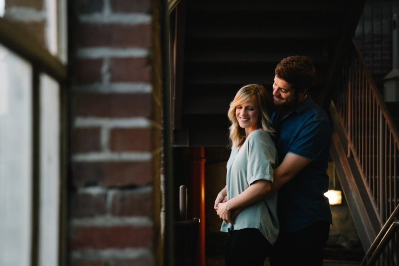 smiling man and woman hugging near stairs