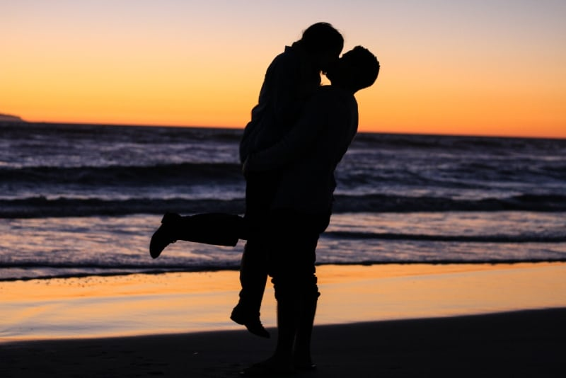 man and woman kissing near sea during golden hour