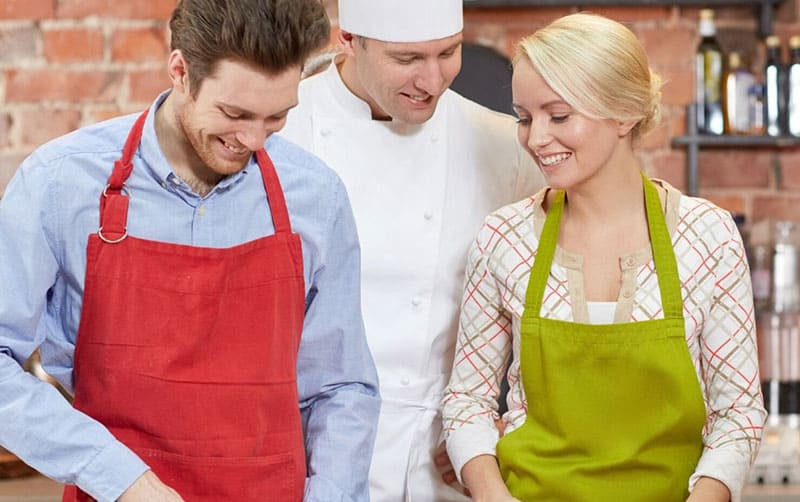 couple learn to cook supervised by a chef