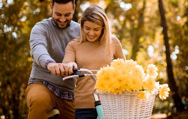 couple sharing a bike with a basket of flower in the park