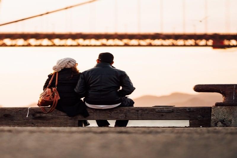 man in black jacket and woman sitting near bridge