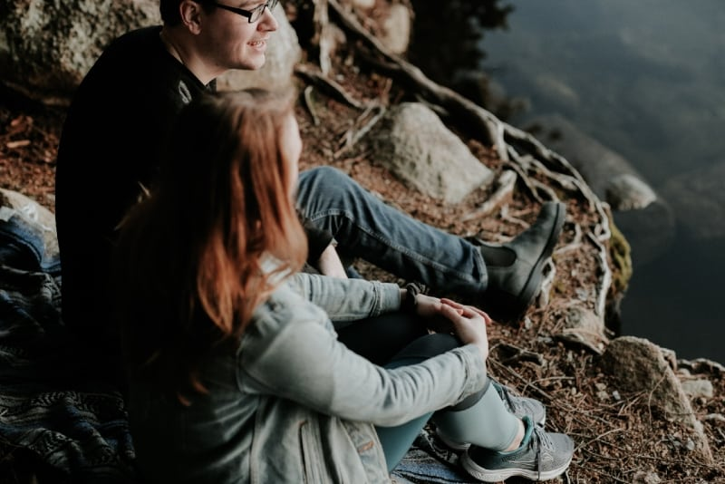 man and woman sitting near water and talking