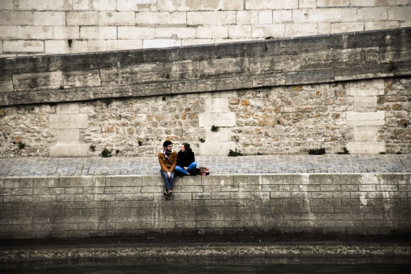 man woman sitting on concrete surface and talking