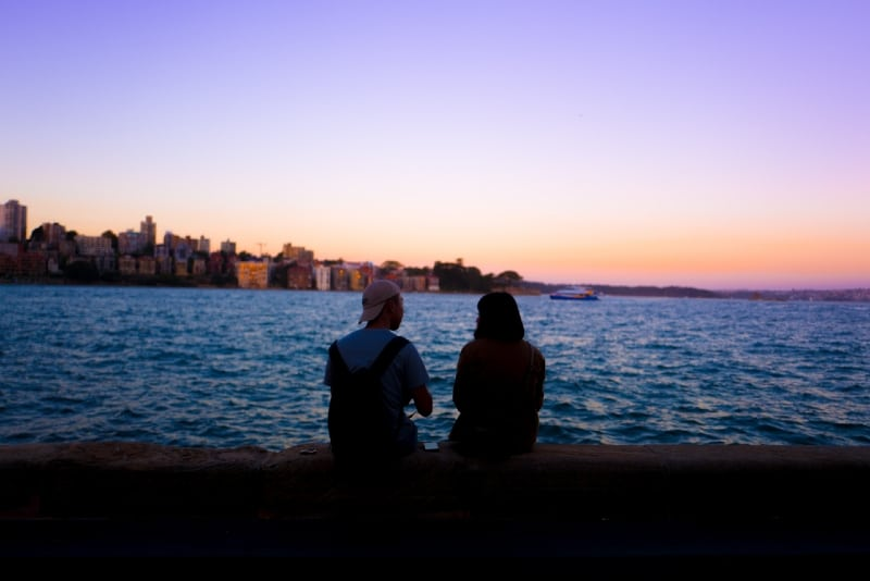 man and woman sitting dock looking at water
