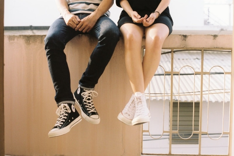 man and woman sitting on concrete fence