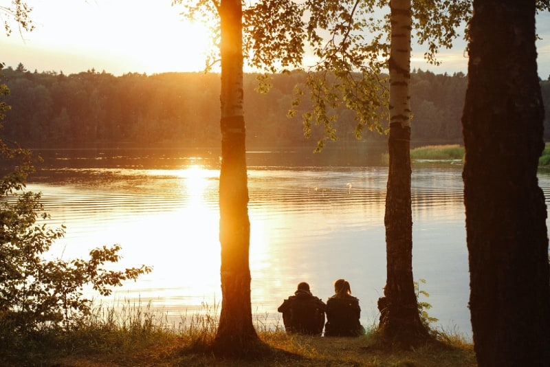 man and woman sitting on grass near water during sunset