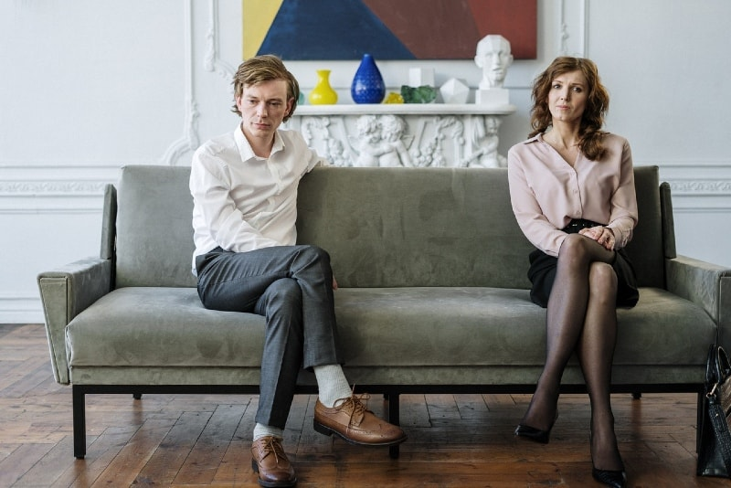 man in white shirt and woman sitting on sofa