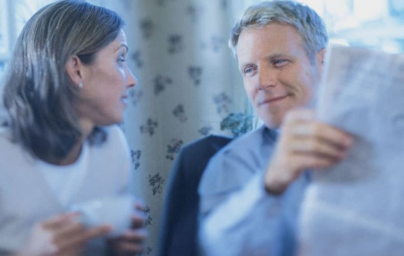 couple talking over a cup of coffee while man reading newspaper