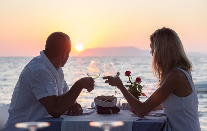 dating couple with wine while looking at the sunset beside the sea