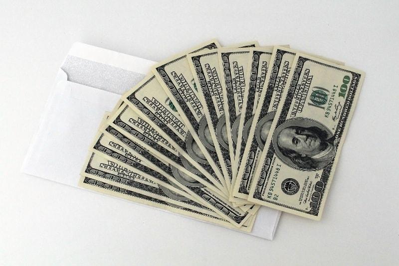 dollar banknotes on white envelope