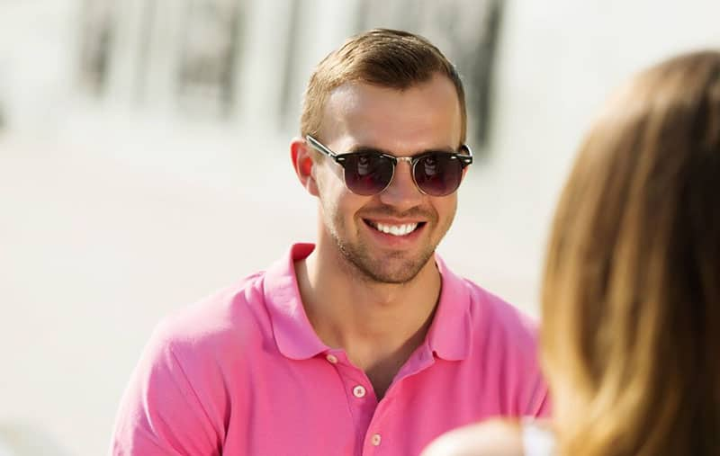 handsome man smiling, wearing pink shirt, in front of a woman