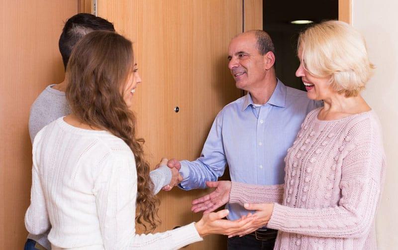 happy couple meeting senior parents at the doorway