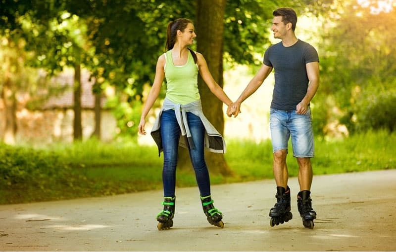 happy couple rollerskating holding hands in the streets of the park