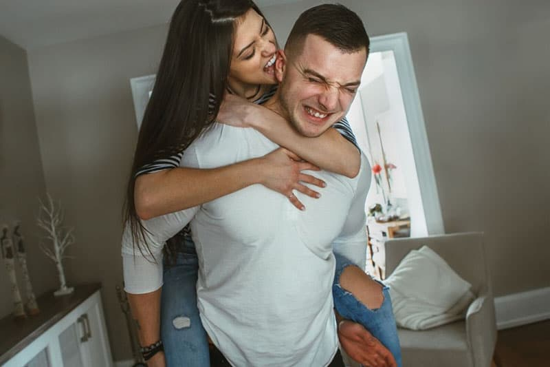 happy funny couple inside living room, woman biting and piggy back on the man