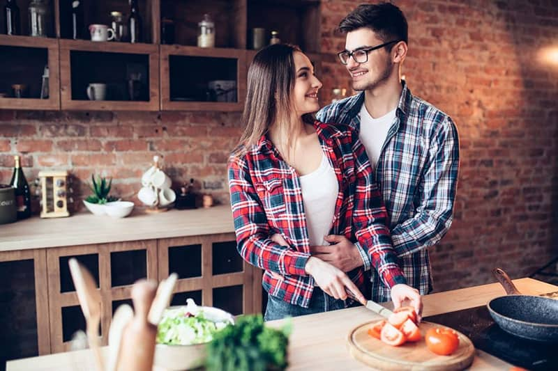 husband hugs wife while slicing tomatoes inside kitchen