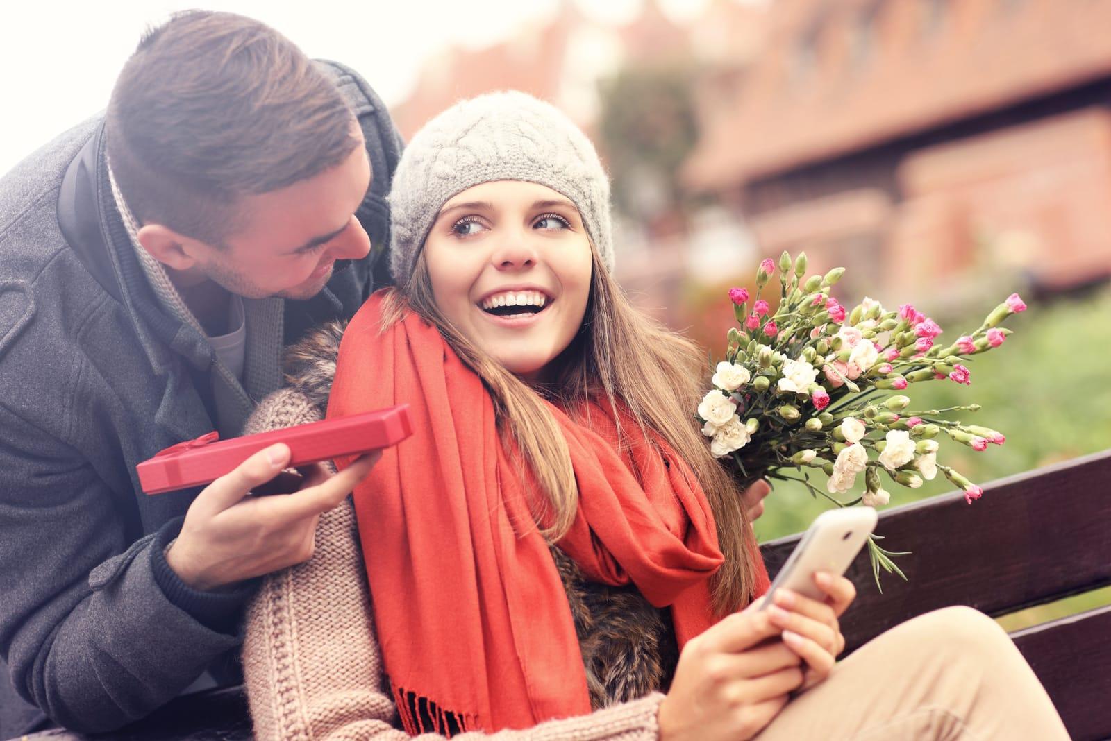 in the park on a bench a man gives a gift to a smiling woman