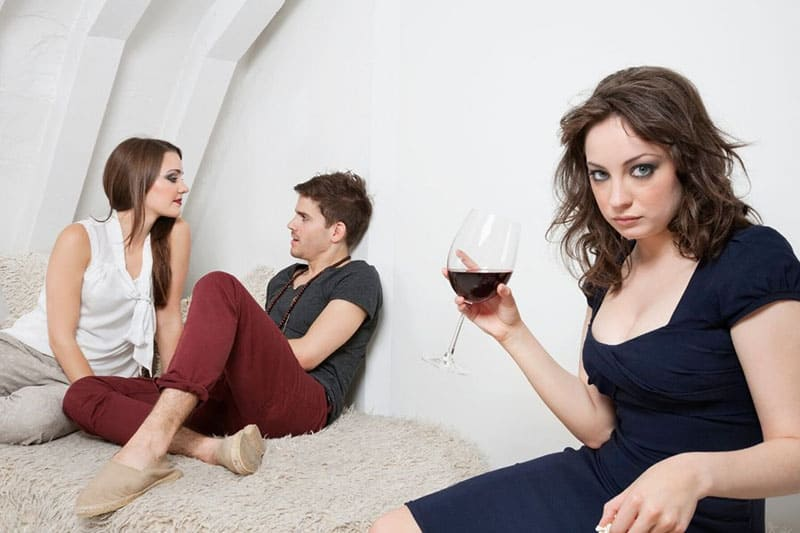 jealous woman sipping wine distant to a sweet couple chatting
