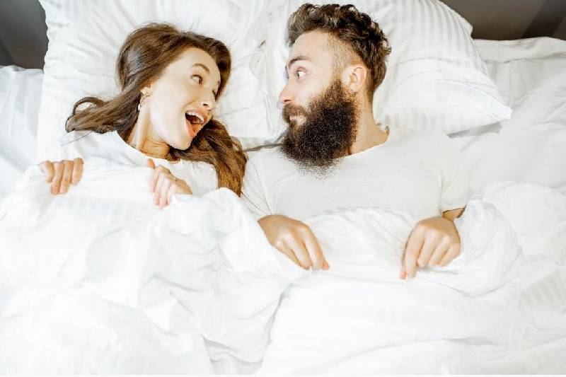 man and woman shocked at each other while lying in bed