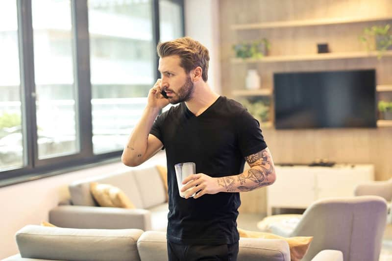 man answering phone while inside the living room bringing glass