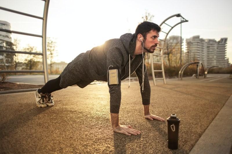 man in gray jacket doing push-ups outdoor