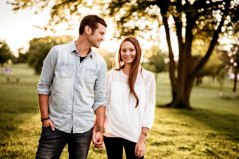 man holding hand of woman near tree