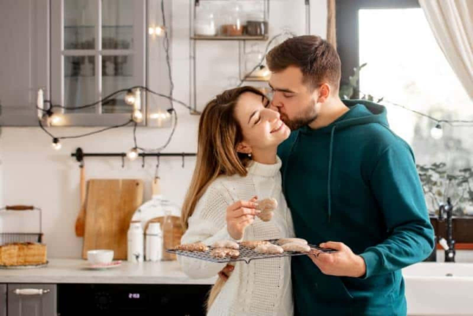 man kissing his woman on cheek and holding cookies
