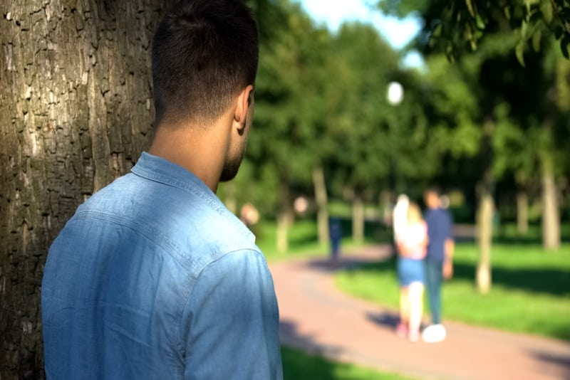 man in blue shirt looking at couple outdoor