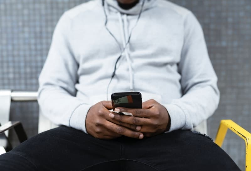 man sitting and typing on his smartphone