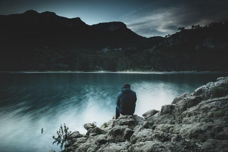 man sitting near lake looking at mountain