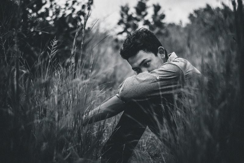 sad man sitting on grass