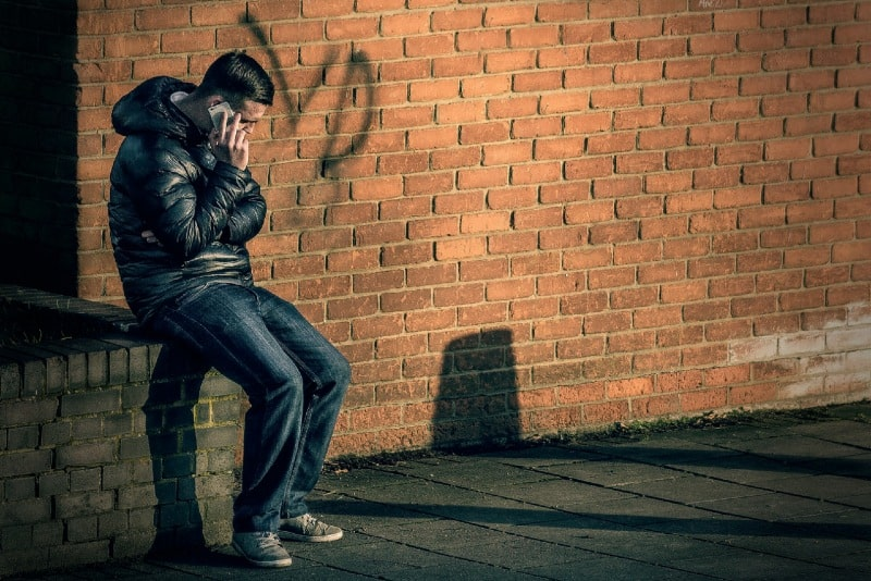 man talking on the phone while sitting on brick wall