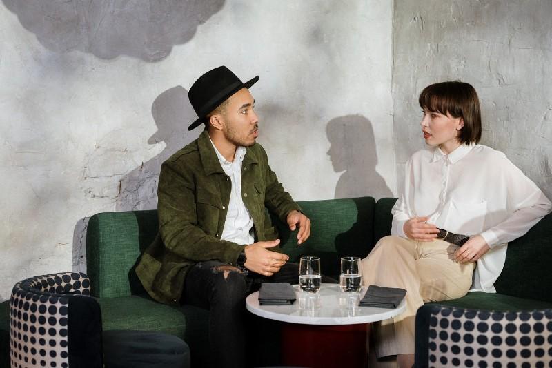 man talking to woman while sitting on green sofa