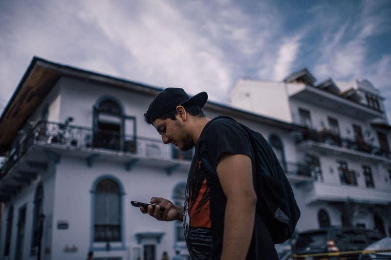 man with cap using his phone