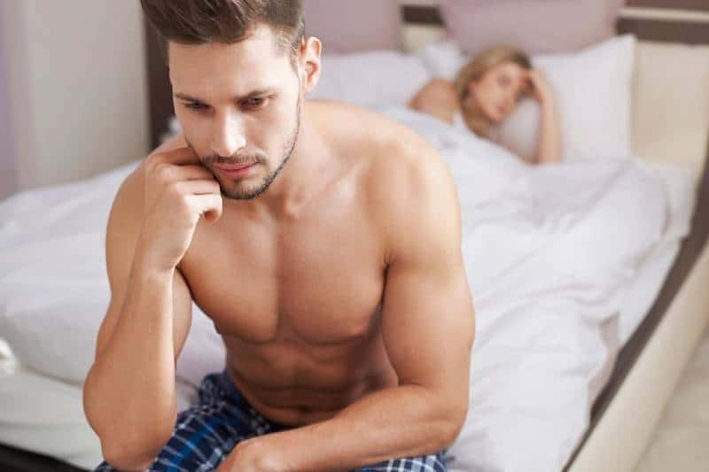 pensive half naked man sitting on bed and a woman sleeping on bed