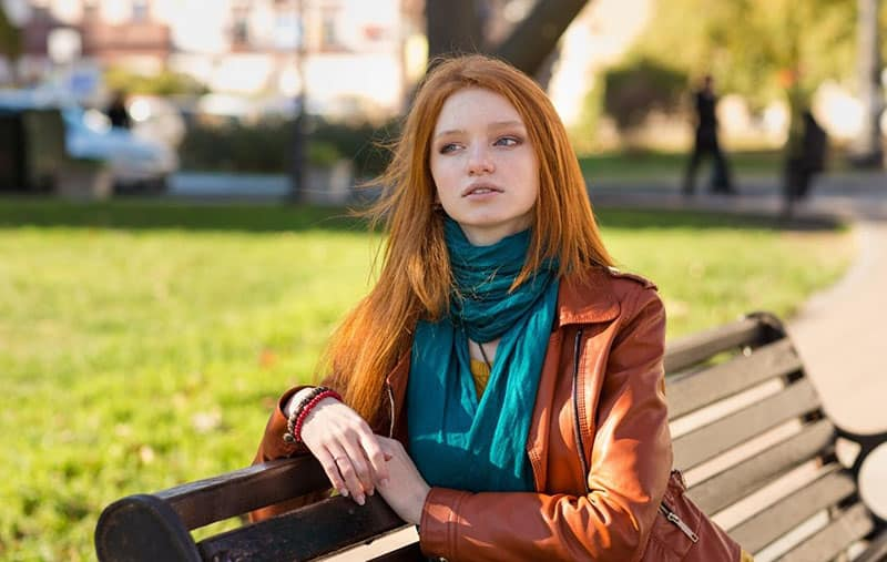 pensive looking woman wearing green scarf sitting on park bench