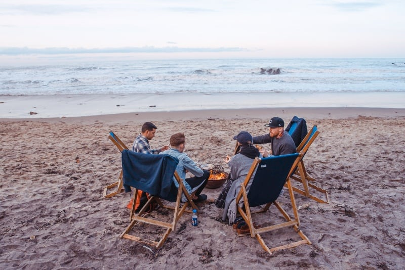 four people sitting on beach lounge near fire pit