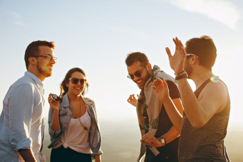 four people laughing while standing outdoor