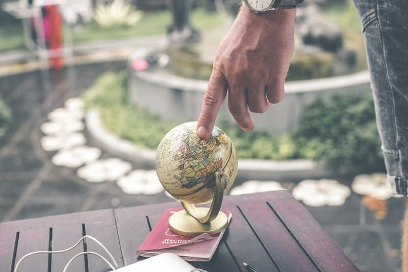 person holding terrestrial globe scale model place on top of the book placed on a table