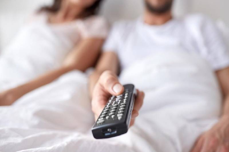 remote control held by a man sitting beside next to a woman
