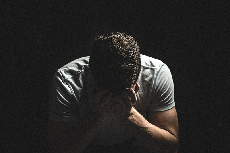 sad guy crying in the dark covering his face with his hands