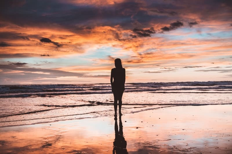 silhouette of woman standing in front of of body of water during golden hour