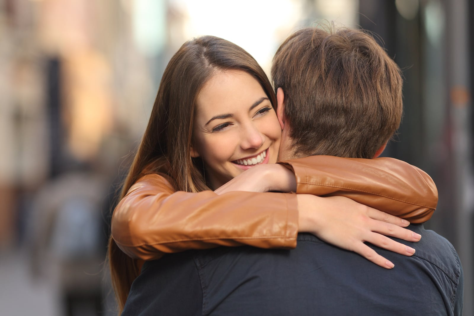 smiling woman in jacket hugging man