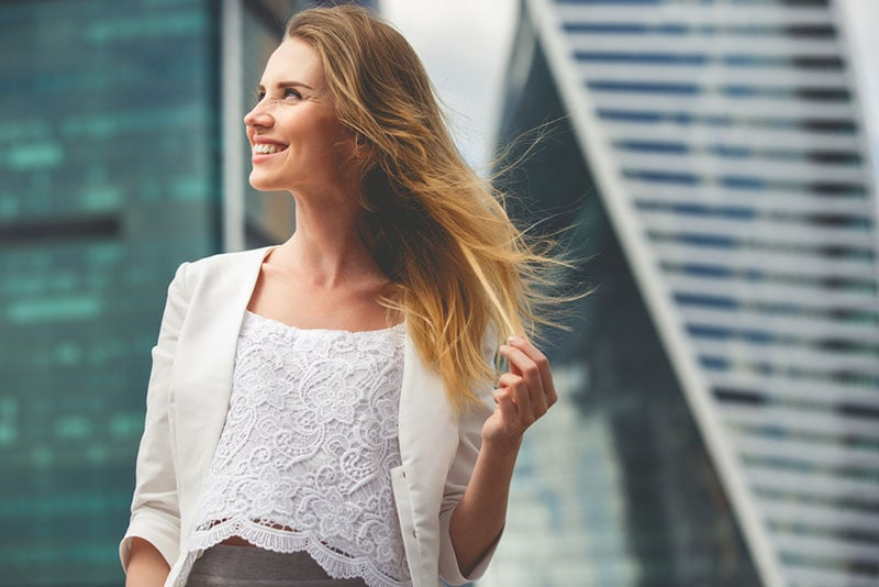 smiling young woman standing on the wind