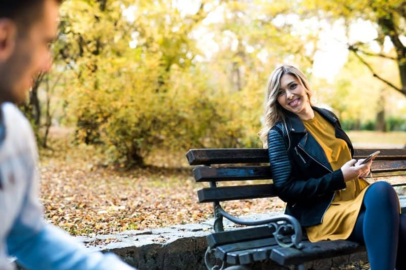 stranger smiling in the park, woman sitting on the bench