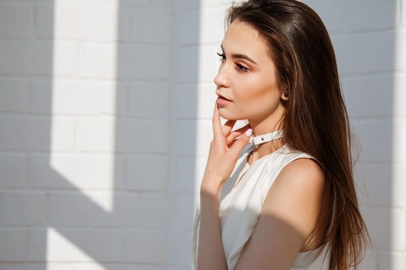 thoughtful lady wearing white top with hands on her face standing near the while wall