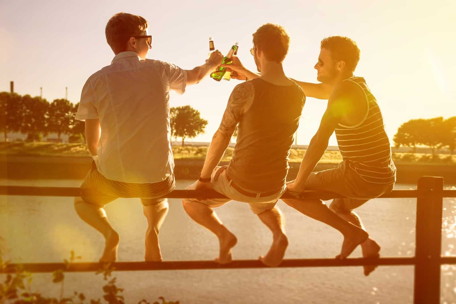 three friends outside at sunset drinking beer