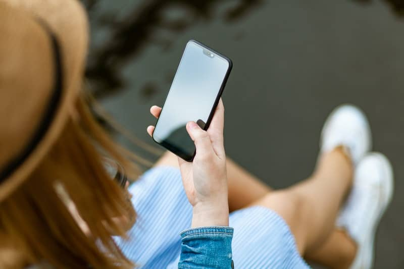 top angle of a woman holding a smartphone wearing a hat